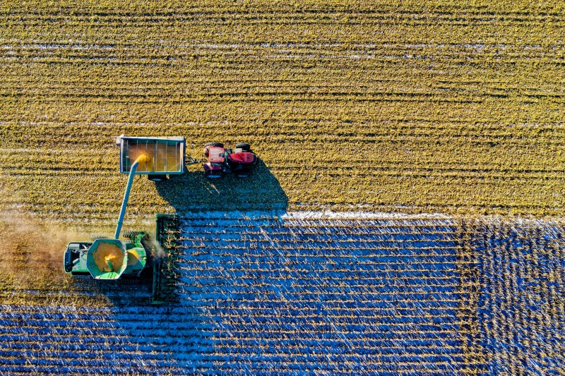 An aerial shot of a field  being harvested